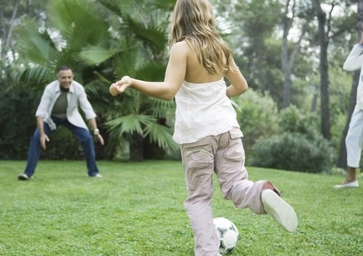Stock Photo: 1569R-9017767 Mature man playing soccer with granddaughter