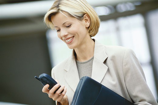 Businesswoman looking at phone, holding laptop : Stock Photo
