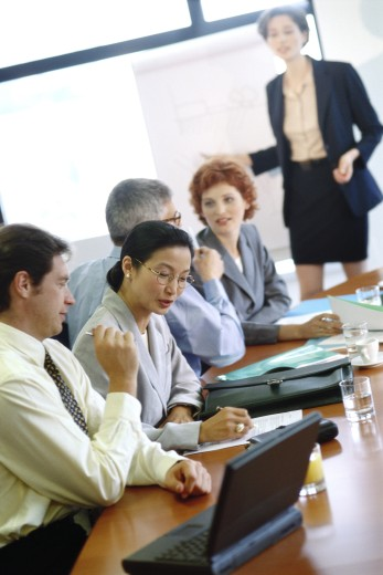 Group of businesspeople sitting around conference table during presentation : Stock Photo