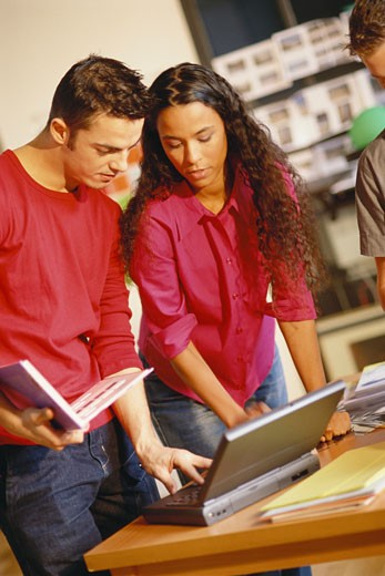 Two young adults looking at laptop, one holding user's manual : Stock Photo