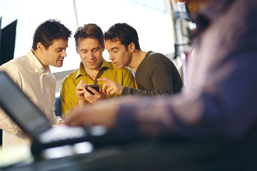 Three young men using electronic organizer, laptop user in foreground : Stock Photo