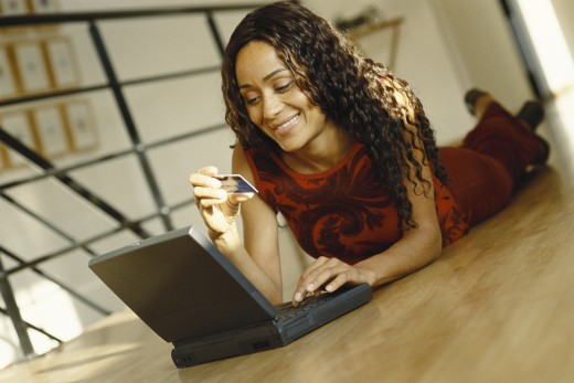 Young woman lying on ground with laptop, holding up credit card : Stock Photo