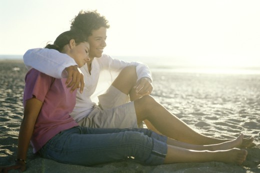 Stock Photo: 1569R-9018399 Teenage couple sitting on beach together