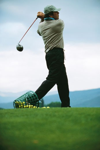 Golfer practicing on driving range, low angle view : Stock Photo