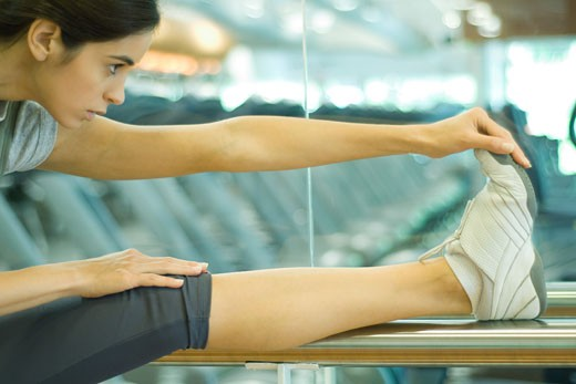 Woman stretching leg on barre : Stock Photo