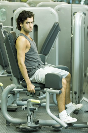 Man working out on weight machine : Stock Photo