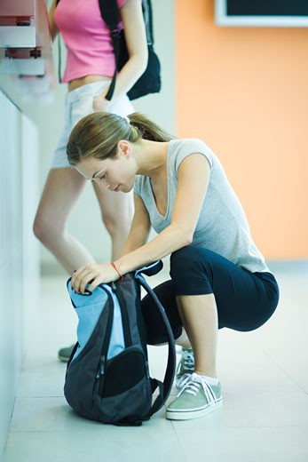 Stock Photo: 1569R-9018917 Young woman at health club counter, crouching and looking in backpack