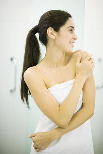 Woman standing wrapped in towel, hand on shoulder, looking away : Stock Photo