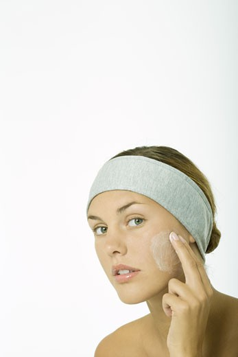 Stock Photo: 1569R-9019171 Young woman applying facial cleanser to cheek, head and shoulders