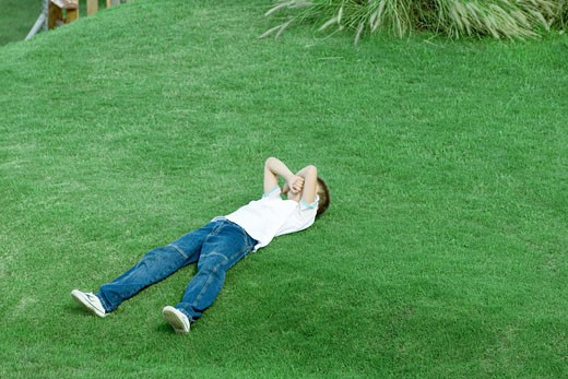 Stock Photo: 1569R-9019248 Boy lying on grass, covering face with arms, full length