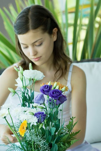 Young woman making fresh flower arrangement : Stock Photo