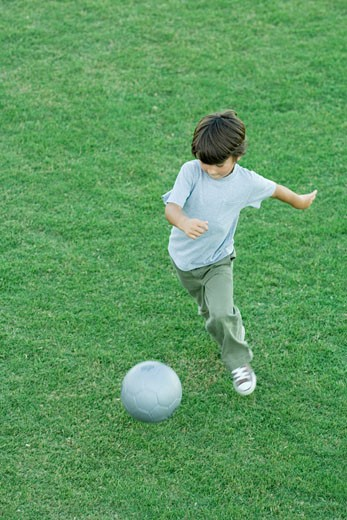 Boy playing soccer on grass, high angle view, full length : Stock Photo
