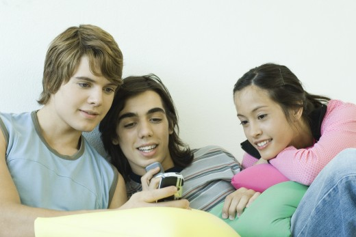 Three teen friends, looking at cell phone : Stock Photo
