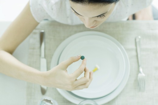 Stock Photo: 1569R-9019459 Woman sitting at empty plate holding vitamin