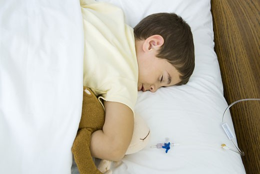 Boy lying in hospital bed, holding stuffed animal : Stock Photo