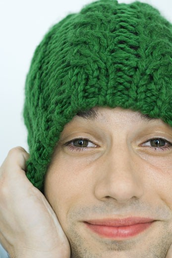 Young man pulling down knit hat over ears, portrait, close-up : Stock Photo