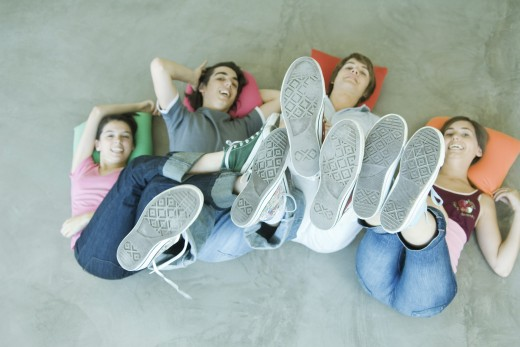 Stock Photo: 1569R-9020091 Four teen friends lying on backs on floor, holding up legs, focus on soles of shoes