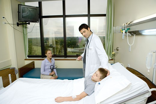 Child lying in hospital bed, doctor standing by side : Stock Photo