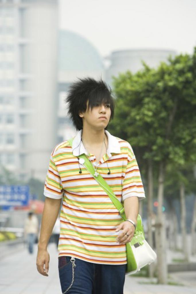 Teenage boy walking in urban setting : Stock Photo