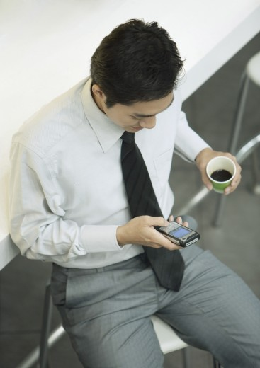 Executive holding cup of coffee and checking cell phone : Stock Photo