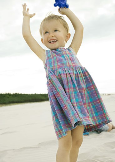 Stock Photo: 1569R-9020336 Little girl standing on beach
