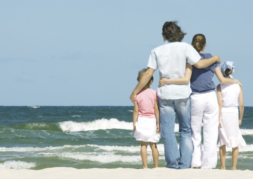 Family standing next to surf, facing ocean, rear view : Stock Photo