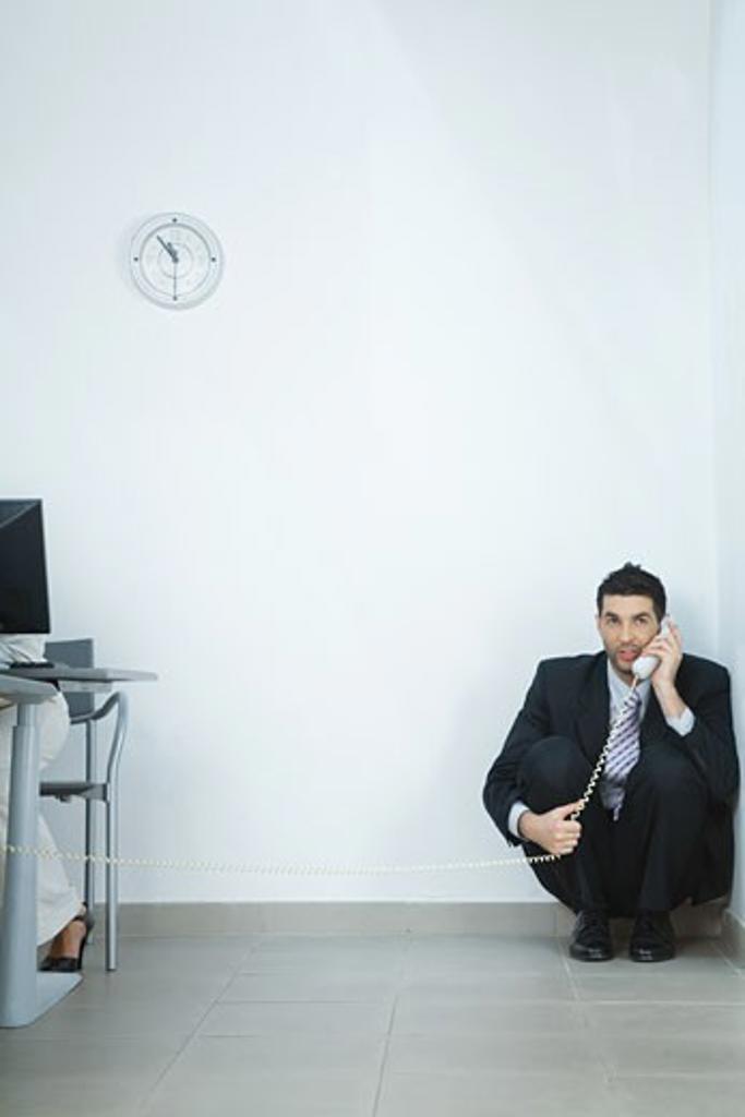 Businessman sitting on floor, in corner, talking on phone : Stock Photo
