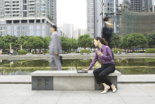 Young woman using laptop outdoors on office park bench : Stock Photo