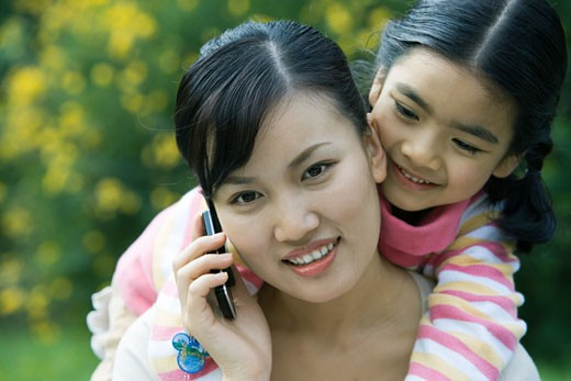 Stock Photo: 1569R-9020627 Woman using cell phone while girl leans over shoulder