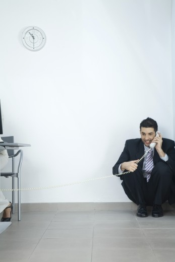 Stock Photo: 1569R-9020689 Businessman sitting in corner, talking on telephone