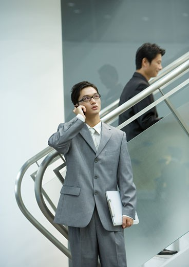 Stock Photo: 1569R-9020743 Businessman using cell phone near staircase