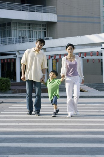 Boy crossing crosswalk, hand in hand with parents, full length : Stock Photo