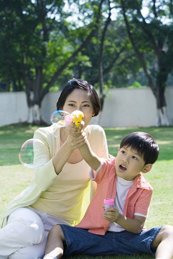 Stock Photo: 1569R-9021150 Mother and son making bubbles