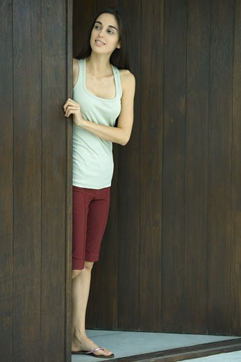 Stock Photo: 1569R-9021808 Woman looking out of doorway, full length