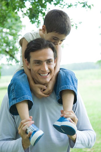 Boy riding on father's shoulders, both smiling : Stock Photo