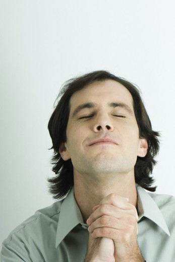 Man clasping hands, head back and eyes closed, head and shoulders, portrait : Stock Photo