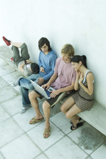 Group of young friends sitting on bench, using laptop : Stock Photo
