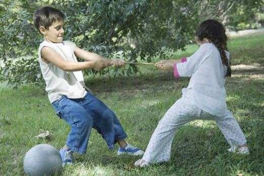 Boy and girl playing tug-of-war : Stock Photo