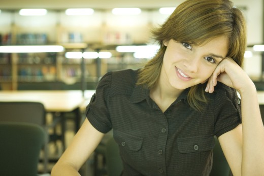 Female college student in library, smiling at camera : Stock Photo