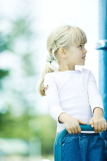 Girl on playground equipment, looking up : Stock Photo
