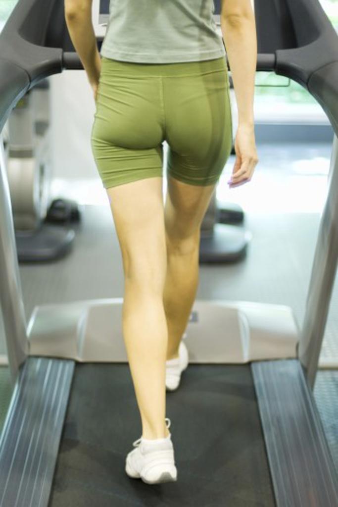 Stock Photo: 1569R-9022279 Woman walking on treadmill, rear view, waist down