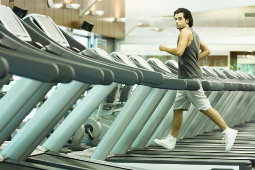 Stock Photo: 1569R-9022354 Man running on treadmill in health club