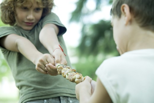 Stock Photo: 1569R-9022533 Two boys playing tug-of-war with grilled kebab