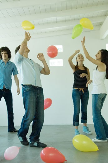 Teenage friends playing with balloons : Stock Photo
