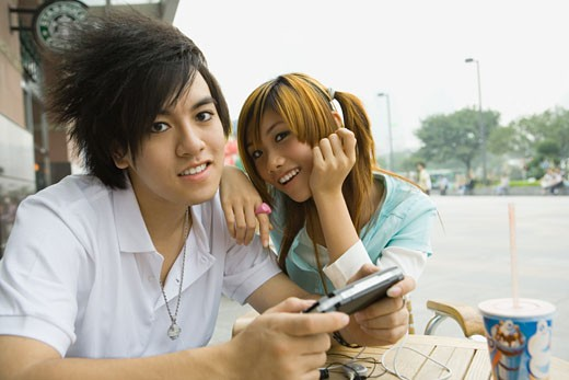 Stock Photo: 1569R-9022697 Teenage couple sitting at outdoor cafe, boy holding video game