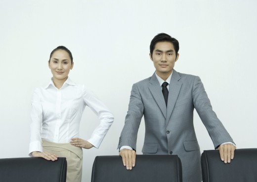 Stock Photo: 1569R-9022704 Businessman and businesswoman standing with hands on backs of chairs, smiling at camera