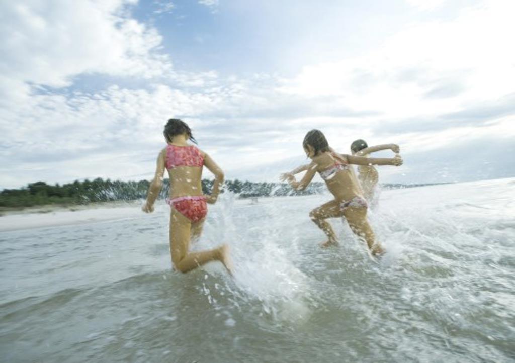 Stock Photo: 1569R-9022756 Children running in surf, rear view