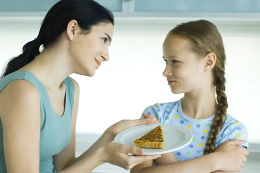 Stock Photo: 1569R-9023239 Girl crossing arms, looking at woman holding piece of quiche