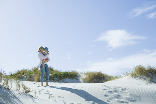 Mother and daughter standing on dune : Stock Photo