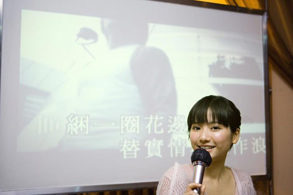 Young woman singing karaoke : Stock Photo